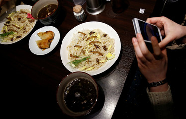 A customer takes pictures of an 'Insect tsukemen' ramen noodle topped with fried worms and crickets 'Ramen Nagi' restaurant in Tokyo
