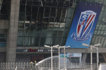 Firefighters are seen outside Hongkou soccer stadium as a fire broke out, in Shanghai