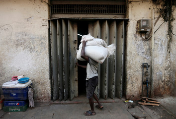 A labourer tries to open a door at a store room as he carries sacks of rice near a main market in Colombo, Sri Lanka
