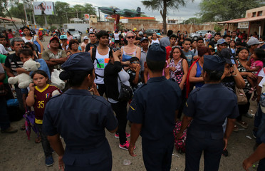 People wait for a military plane at an air force base to travel outside Piura as roads are closed after floods, in Piura, northern Peru