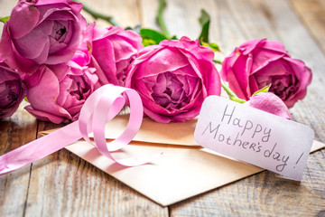 present design with Mother's day text and greeting-card on wooden desk