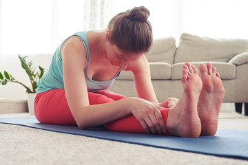 Good-looking female stretching in seated forward bend pose