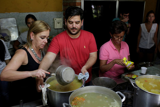 Diego Prada, Maria Luisa Pombo and other volunteers of the Make The Difference (Haz La Diferencia) charity initiative prepare soup to be donated, at Maria Luisa's kitchen in Caracas