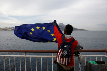 An African migrant holds a European Union flag on board a ferry to Algeciras after having awaited in CETI, the short-stay immigrant centre in Spain's north African enclave of Ceuta to be transferred to mainland Spain