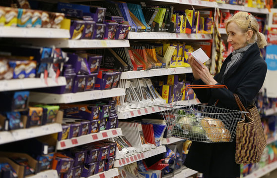 A shopper checks her shopping list in a supermarket in London
