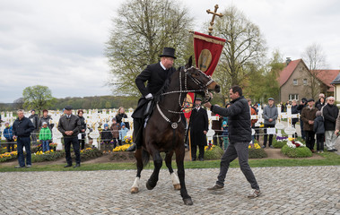 A Sorbian man dressed in a black tailcoat rides a decorated horse during an Easter rider procession in Ralbitz