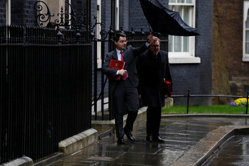 Britain's Secretary of State for Northern Ireland James Brokenshire struggles with an umbrella as he leaves 10 Downing Street with Secretary of State for Scotland David Mundell after a cabinet meeting ahead of the budget in London