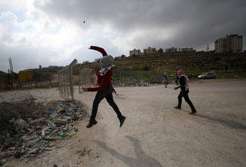 Palestinian protester hurls stones towards Israeli troops during clashes near Israel's Ofer Prison near the West Bank city of Ramallah