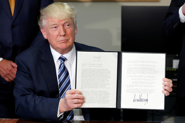 U.S. President Donald Trump holds up an executive order after signing it during a ceremony with Treasury Secretary Steve Mnuchin at the Treasury Department