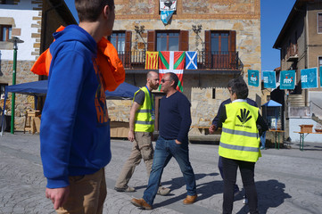 People walk past a house displaying Basque, Catalan and Scottish flags on the day of a non-binding consultation asking citizens if they wish to be part of an independent Basque state, in Larrabetzu