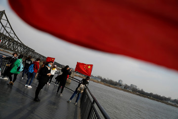 Tourists are seen taking pictures beside Chinese flags on the Broken Bridge in Dandong