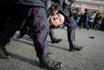 Law enforcement officers detains an opposition supporter during a rally in Moscow, Russia
