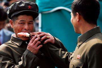 Men share an ice-cream in Pyongyang