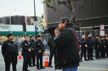 Tom Goldtooth of the Indigenous Environmental Network speaks on a bullhorn while police form a line near a group of people gathered outside the Oscar ceremony to protest the Dakota Access oil pipeline, in Hollywood