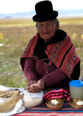 An Aymara woman shows food and drinks made with quinoa during the sweet quinoa promotion at the Canaviri