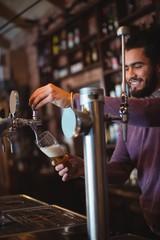 Bar tender filling beer from bar pump