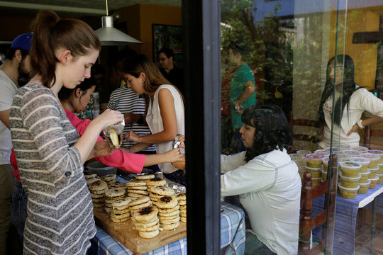 Volunteers at Make The Difference (Haz La Diferencia) charity initiative prepare soup and fill in arepas to be donated, at the home kitchen of one of the volunteers in Caracas