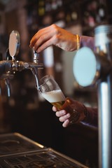 Close-up of bar tender filling beer from bar pump