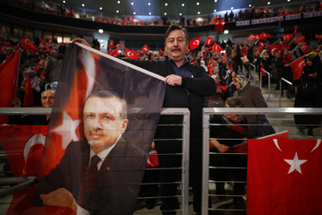 A supporter of Turkish President Erdogan holds a flag before Turkish Prime Minister Yildirim is expected to addresses a crowd in Oberhausen