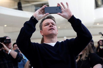 Actor Matt Damon takes a photo with his mobile phone in the World Trade Center Oculus transportation hub beneath a portion of 'The Water Clouds by Stella Artois', a public art installation of balloons to recognize World Water Day in New York