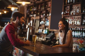 Female bar tender interacting with customer