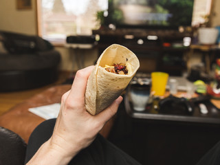 Holding Breakfast Burrito in Living Room