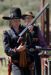 Jessica Healey, 12, under the character name 'Rosebud', empties shotgun shells during competition at the Women of the West shooting contest at the Namoi Pistol Club in Gunnedah in rural New South Wales, Australia