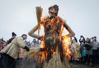 Revellers burn an effigy of Kostrubatyi Did, a symbol of winter, during the celebration of Maslenitsa also known as Kolodiy, a pagan holiday marking the end of winter, in Kiev, Ukraine