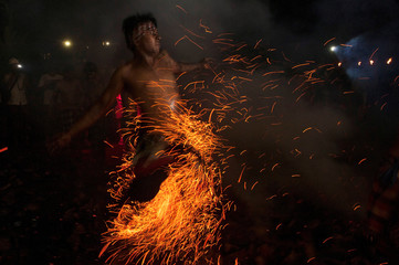 """A Balinese Hindu runs through burning coconut husks during a """"Mesabatan Api"""" ritual on the eve of Nyepi, which is a day of silence for self-reflection to celebrate the new year in Gianyar, Bali, Indonesia"""
