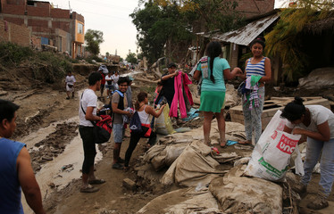 Volunteers give clothes to victims, after rivers breached their banks due to torrential rains, causing flooding and widespread destruction in Cajamarquilla, Lima