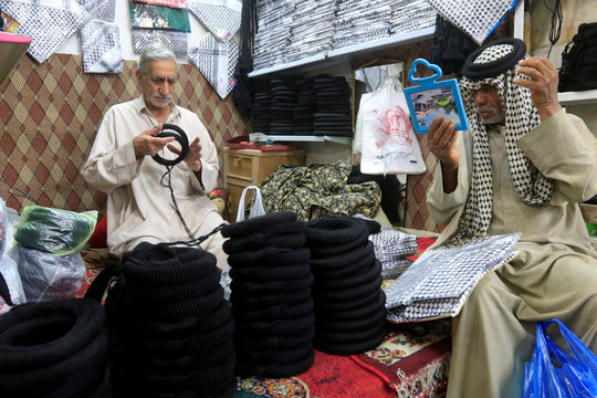A man looks in a mirror as he buys a keffiyeh, a traditional Arabic headdress, at a store in a market in Najaf