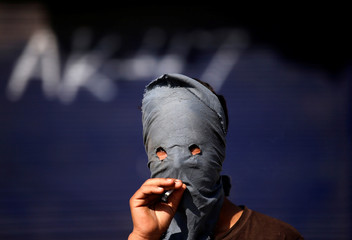 A masked Kashmiri demonstrator smokes a cigarette during a protest against the recent killing of a civilian, in Srinagar