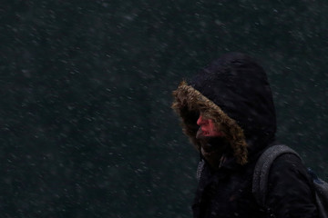 A man walks with his hood on as it snows in Times Square New York