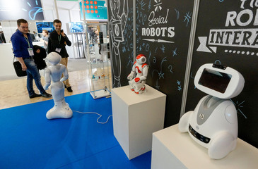 Visitors look at SoftBank humanoid robots Pepper and Nao and Blue Frog Robotics robot named Buddy at the SIdO, the Connected Business trade show, in Lyon