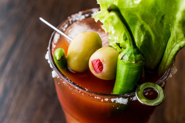 Bloody Mary Cocktail with green olive, pepper, lettuce, salt and ice.