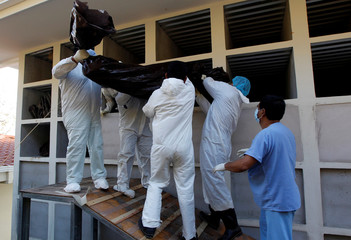 Morgue workers place a bag containing an unidentified body into a niche at a cemetery in Tegucigalpa