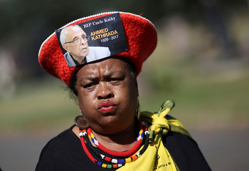 A mourner arrives wearing a hat bearing a picture of Ahmed Kathrada, who was sentenced to life imprisonment alongside Nelson Mandela, during his funeral at the Westpark Cemetery in Johannesburg