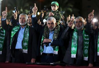 Son of senior Hamas militant Mazen Fuqaha sits on the shoulders of Hamas Gaza Chief Yehya Al-Sinwar during a memorial service for Fuqaha, in Gaza City