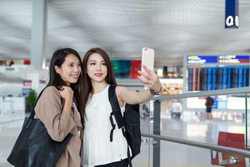 Women taking selfie by mobile phone in Hong Kong international airport