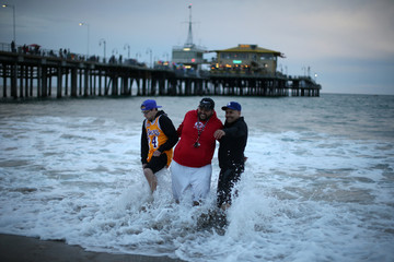 People react as they are hit by a wave while having their photo taken in the Pacific Ocean on a cold spring solstice day in Santa Monica