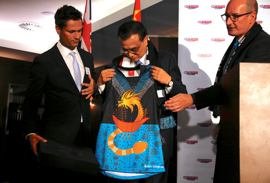 Chinese Premier Li Keqiang is presented with a specially designed Port Adelaide player jersey before the start of an Australian Football League (AFL) game at the Sydney Cricket Ground (SCG) in Sydney