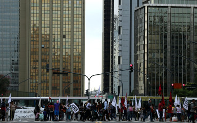 People cross the street as demonstrators block an avenue in downtown Buenos Aires