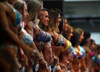 Women participate during the Mr. Olympia Amateur South America bodybuilding competition in Medellin