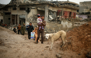 Displaced Iraqis flee their homes on a rainy day as Iraqi forces battle with Islamic State militants in western Mosul