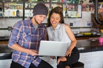 Happy friends using laptop in restaurant