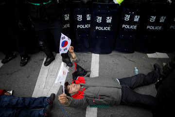 A supporter of impeached President Park Geun-hye lies in front of a barricade of riot police during a protest after Park's impeachment was accepted, near the Constitutional Court in Seoul