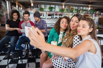 Female friends taking selfie at restaurant