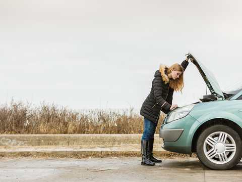 Blonde woman and broken down car on road