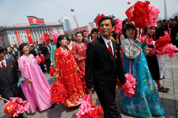 People carry plastic flowers after a military parade marking the 105th birth anniversary of North Korea's founding father, Kim Il Sung in Pyongyang