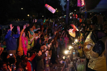 Float riders throw gifts to people watching the Bacchus parade during Mardi Gras in New Orleans, Louisiana